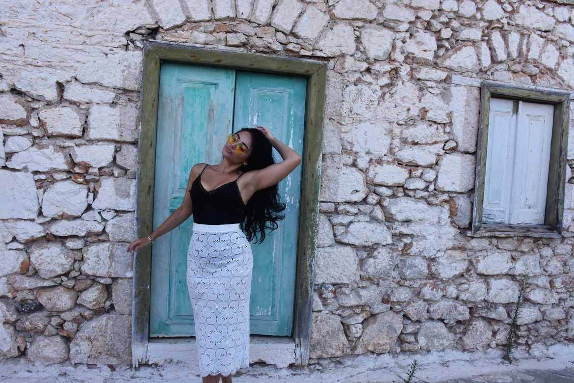 A female blogger in front of a colored full traditional house in Greece and wearing white lace pencil skirt and black body con .