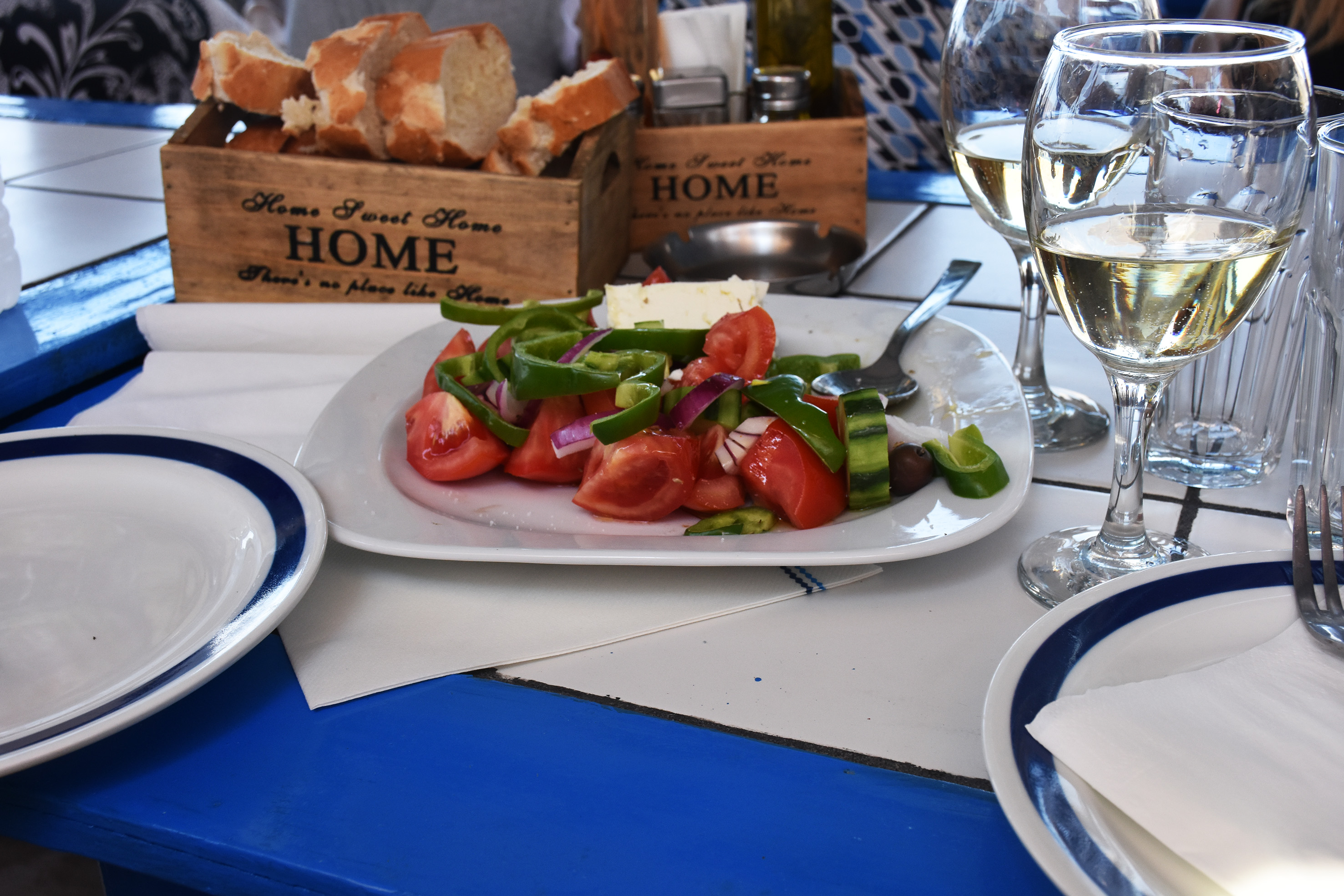 greek salad , bread and a glass of wine in a restaurant by the sea in Simi , Greece